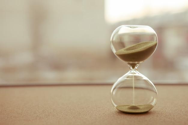 Arena corriendo a través de las bombillas de un reloj de arena que mide el tiempo que pasa