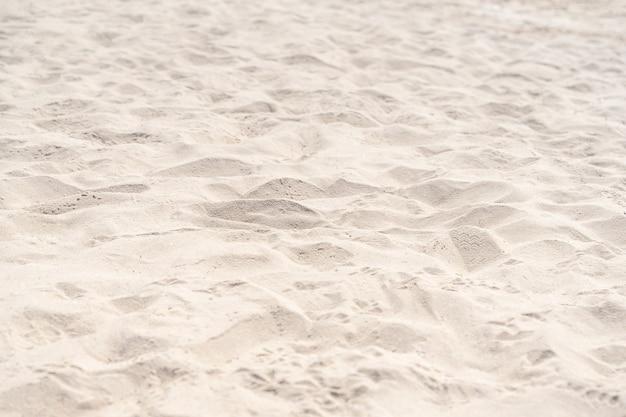 Arena en la playa para el fondo. textura de arena de playa marrón como fondo. de cerca.