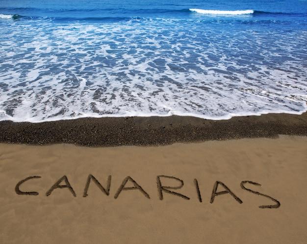 Arena de playa marrón con la palabra escrita canarias