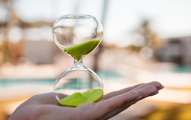 Arena que fluye en un matraz de vidrio - reloj de arena en la mano de una niña sobre un fondo claro borroso