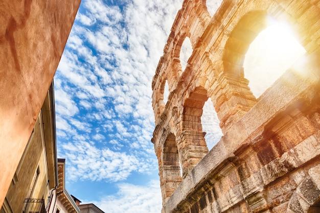 Arena de verona, antiguo anfiteatro romano en italia durante el amanecer y el cielo azul con nubes.