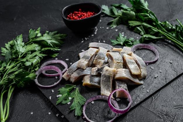 Arenques salados con aros de cebolla. fondo negro. vista superior