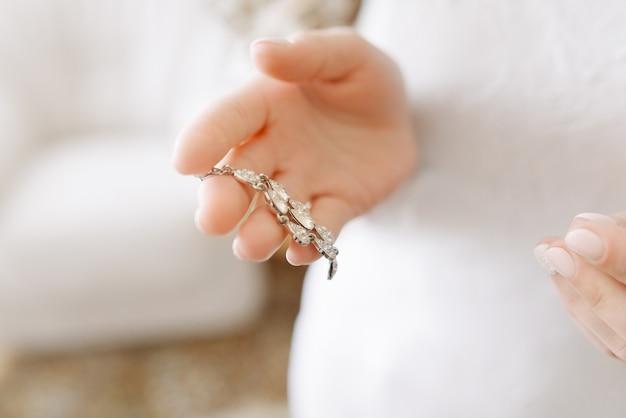 Arete con piedras en la mano de la novia o una niña con un vestido blanco, primer plano