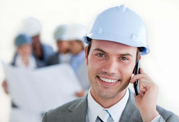 Arhitect sonriente con un casco en el teléfono