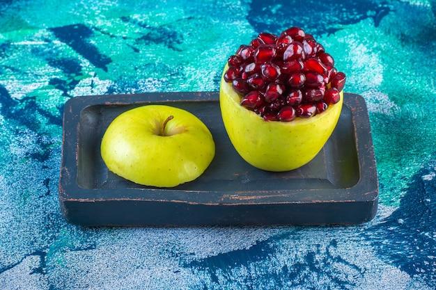 Arilos de manzana y granada en rodajas sobre una placa de madera