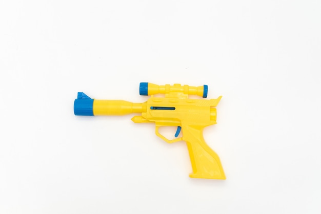 Arma amarillo plástico aislado en el fondo blanco