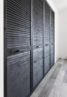 Armario de madera negra decorado con persianas, armario con decoración de persianas.