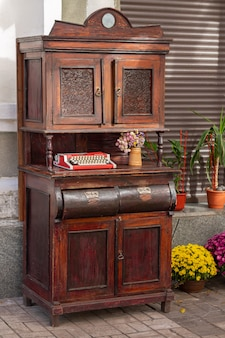 Armario de madera vintage con vieja máquina de escribir y flores al aire libre