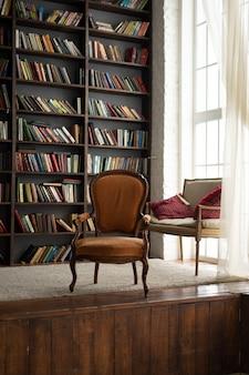 Armario viejo con muchos libros y una silla al lado.