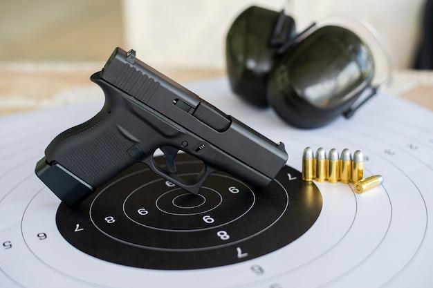 Armas de fuego con munición en la práctica de tiro al blanco de papel.