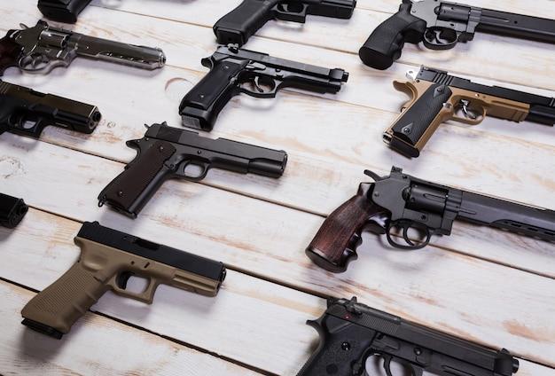 Armas de fuego pistola. el primer el arma miente en un fondo blanco de madera.