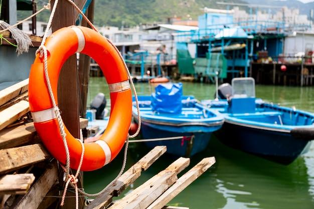 Aro salvavidas y barcos de pesca en el pueblo pesquero tai o en la isla de lantau, hong kong