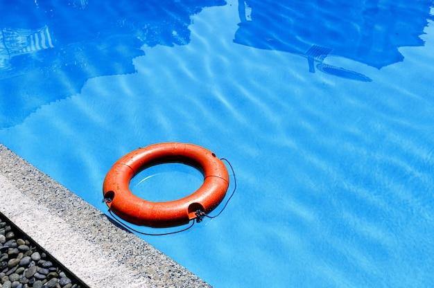 Aro salvavidas naranja flotando en la piscina de superficie