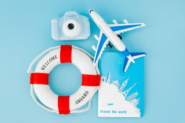 Aro salvavidas, pasaportes, cámara y modelo de avión.