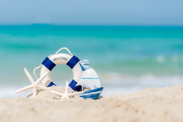 Aro salvavidas en la playa de arena con estrellas de mar y barco de pesca. concepto de verano