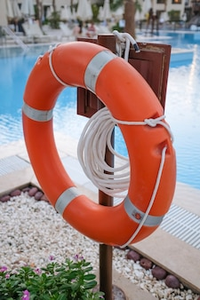 Aro salvavidas rojo y cuerdas para salvar vidas al ahogar personas cerca de la piscina. foto de alta calidad