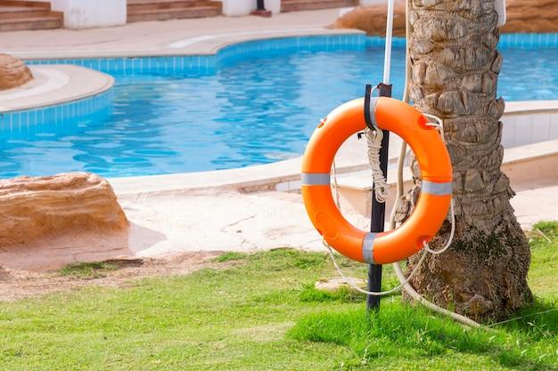 Aro salvavidas en la valla, junto a la piscina de vacaciones en el hotel