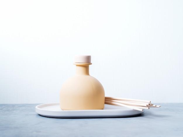Aroma reed difusor de la casa fragancia con palos de ratán sobre un fondo claro