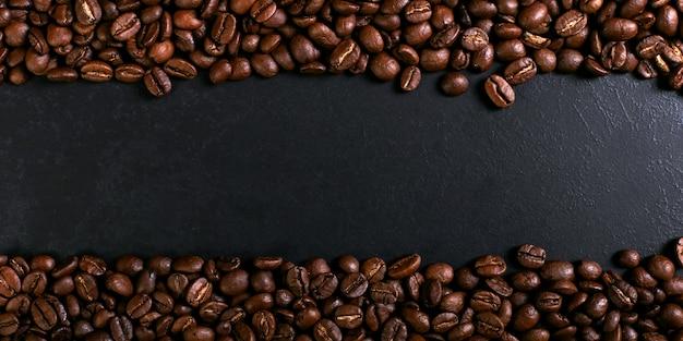 Aroma tostado granos de café sobre la mesa rústica, fondo marrón de la bandera.