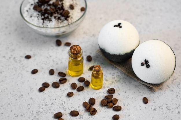 Aromaterapia y concepto de spa. sal de spa con aroma a café cerca de jabón, aceite de spa y lufa sobre fondo blanco vista superior