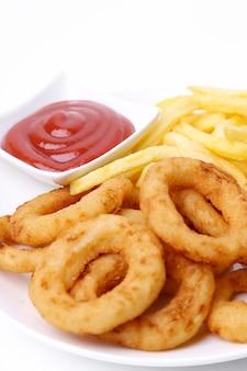 Aros de cebolla y papas fritas con salsa de tomate