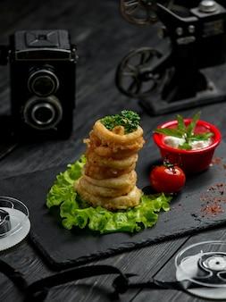 Aros de cebolla rebozados con salsa y tomate