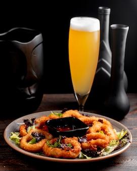 Aros de cebolla servidos con salsa de lechuga y cerveza