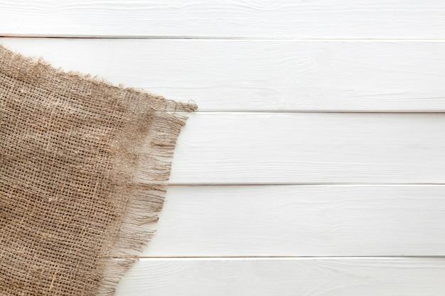 Arpillera sobre fondo blanco de madera