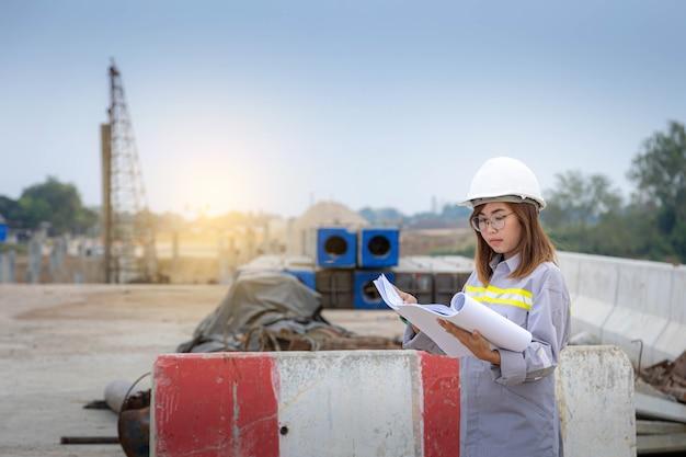 Una arquitecta líder de pie en la construcción del puente, con un casco de seguridad y sosteniendo el plano del proyecto.