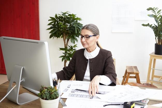 Arquitecta madura concentrada haciendo dibujos, comparándolos con medidas en computadora. mujer ingeniera calificada que presenta la especificación electrónica, mirando la pantalla con expresión enfocada