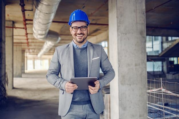 Arquitecto sin afeitar caucásico alegre guapo en traje, con casco en la cabeza y tableta en manos de pie en el edificio en proceso de construcción