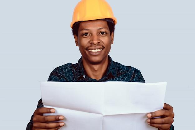 Arquitecto afroamericano en casco con plano.