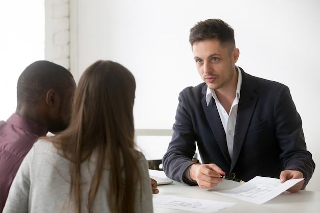 Arquitecto, agente inmobiliario o diseñador que consulta a una pareja interracial con el plan de la casa.