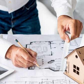 Arquitecto de alto ángulo trabajando en planos de construcción