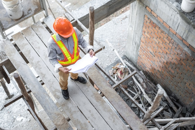 Arquitecto asiático con documentos del proyecto y usando casco en el sitio de construcción