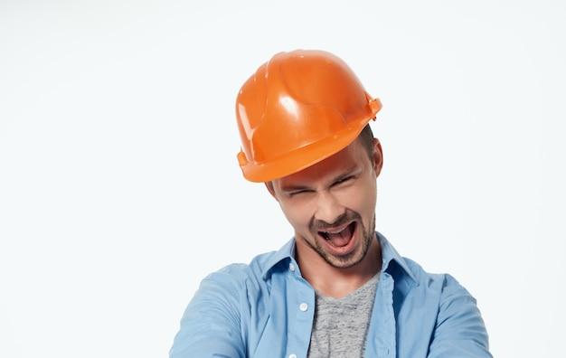 Arquitecto en casco naranja y camisa desabrochada gesticulando con las manos vista recortada blanca