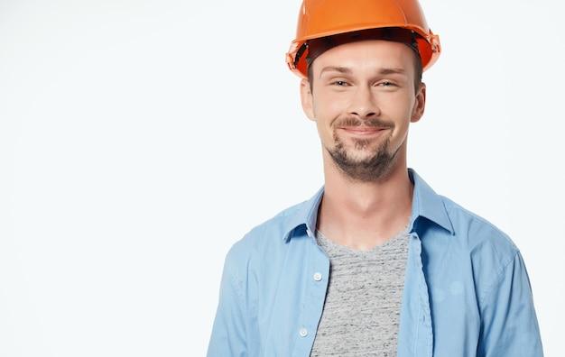 Arquitecto en casco naranja y camisa desabrochada gesticulando con las manos vista recortada fondo blanco.