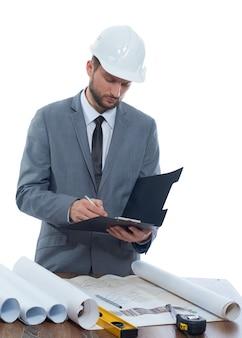 Arquitecto en un casco de protección que hace notas en su sujetapapeles aislado en el fondo blanco.