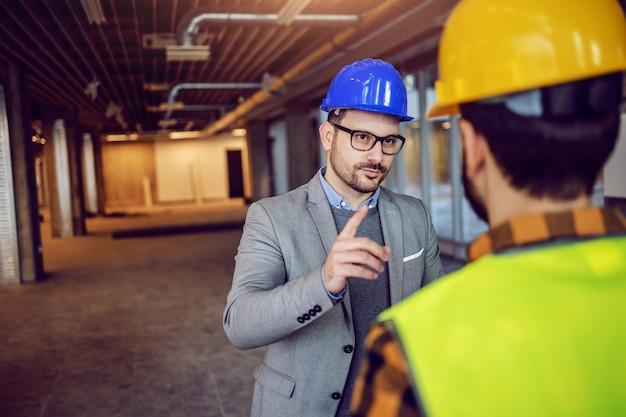 Arquitecto caucásico serio que llama la atención al trabajador de la construcción de la importancia del proyecto en el que está trabajando.