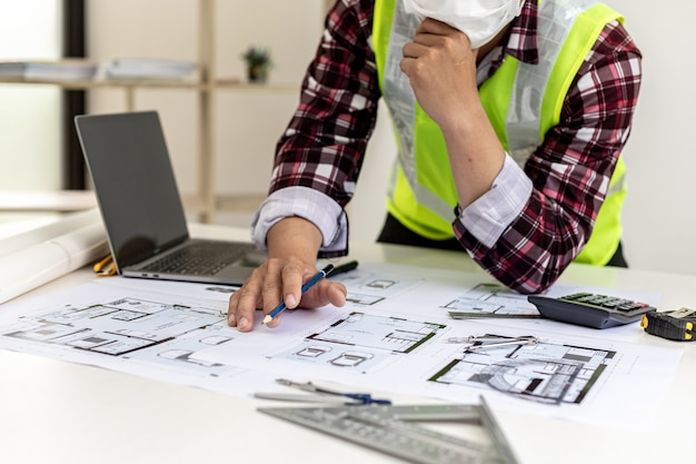 El arquitecto comprueba los planos que ha diseñado, está comprobando la exactitud y corrigiendo los diseños de la casa antes de llevarlos al cliente. ideas de diseño e interiorismo.