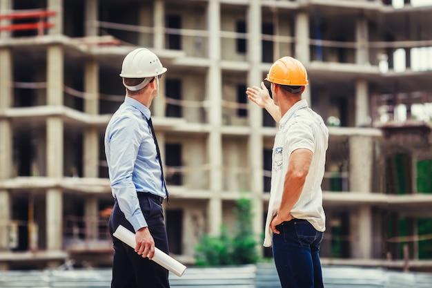 Arquitecto y constructor discutiendo en el sitio de construcción