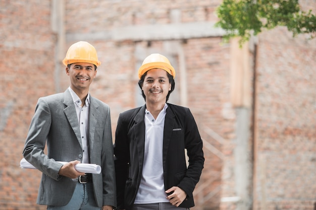 Arquitecto y constructor de pie frente a la casa sin terminar