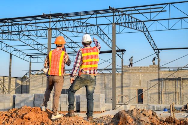 Arquitecto de dos jóvenes en un sitio de construcción de edificios