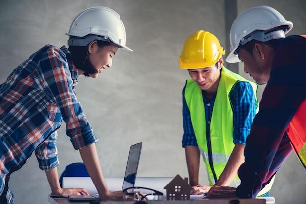 Arquitecto e ingeniero que trabaja en un documento de dibujo sobre la planificación del proyecto y el progreso del horario de trabajo en el sitio de construcción del edificio