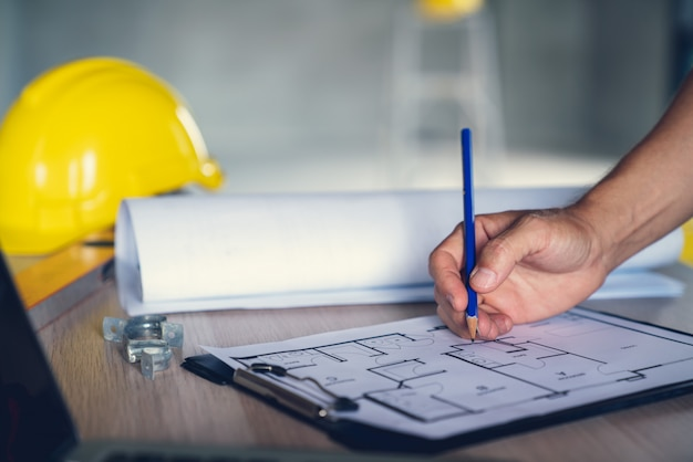 Arquitecto e ingeniero trabajando en un documento de dibujo sobre la planificación del proyecto y el progreso del cronograma de trabajo en el sitio de construcción del edificio de viviendas,