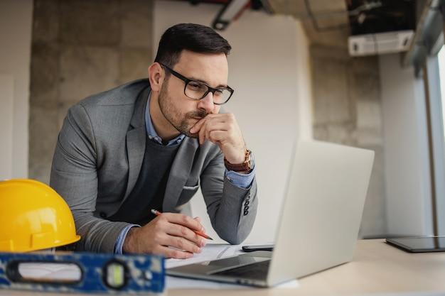 Arquitecto enfocado apoyado en el escritorio en el sitio de construcción con un lápiz en la mano y mirando la computadora portátil.