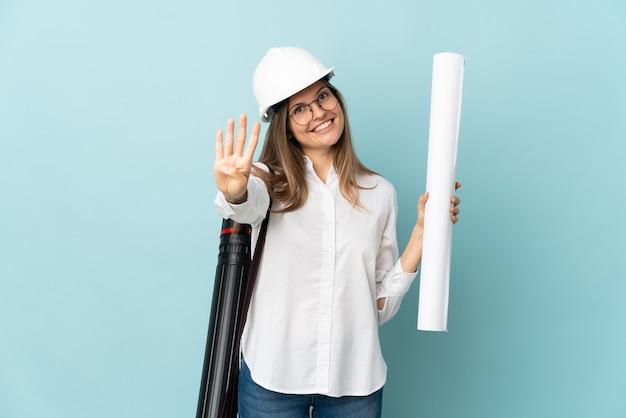 Arquitecto eslovaco chica sosteniendo planos aislados en la pared azul feliz y contando cuatro con los dedos