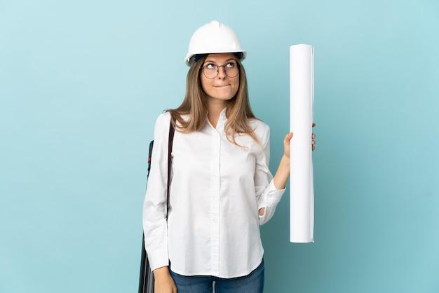 Arquitecto eslovaco chica sosteniendo planos aislados en la pared azul y mirando hacia arriba