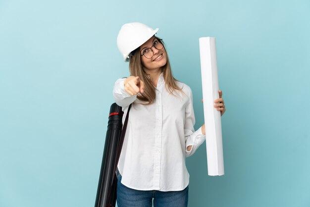 Arquitecto eslovaco chica sosteniendo planos aislados sobre fondo azul apuntando al frente con expresión feliz