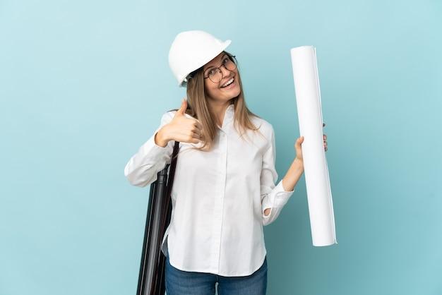 Arquitecto eslovaco chica sosteniendo planos aislados sobre fondo azul con los pulgares hacia arriba porque algo bueno ha sucedido